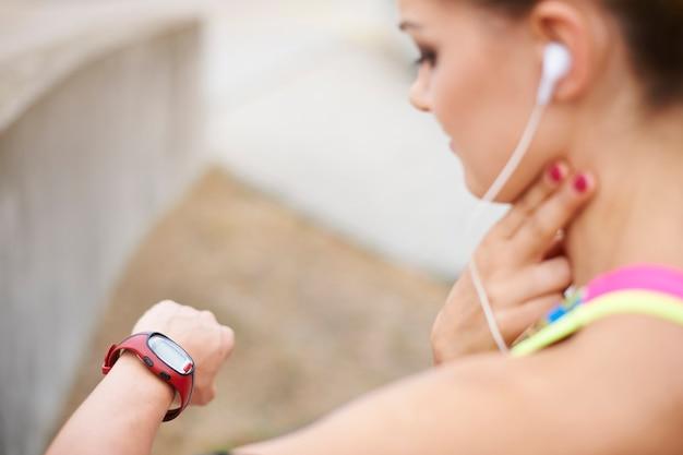 屋外で運動する若い女性。私の脈拍は元気なので続けることができます