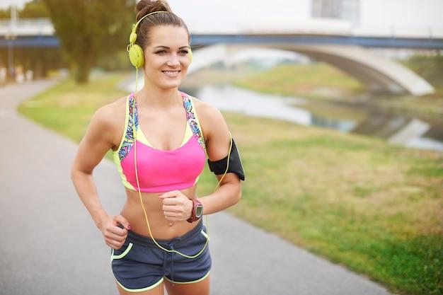 屋外で運動する若い女性。公園はジョギングに行くのに私のお気に入りの場所です