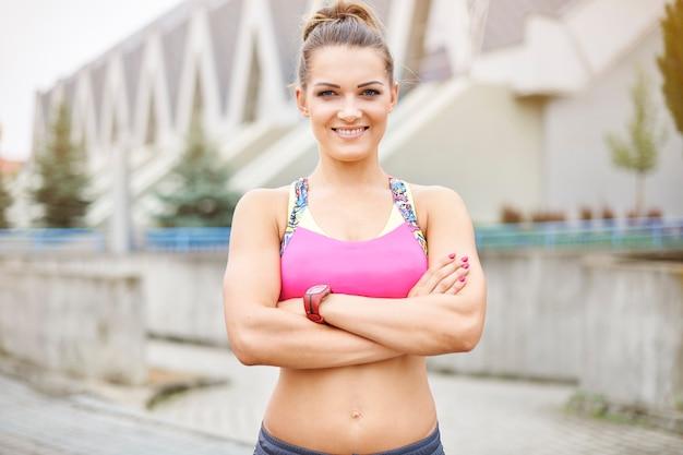 屋外で運動する若い女性。ジムの前でフィットネストレーナーの肖像画