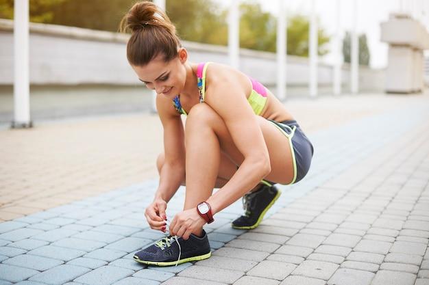 屋外で運動する若い女性。運動前の準備は非常に重要です