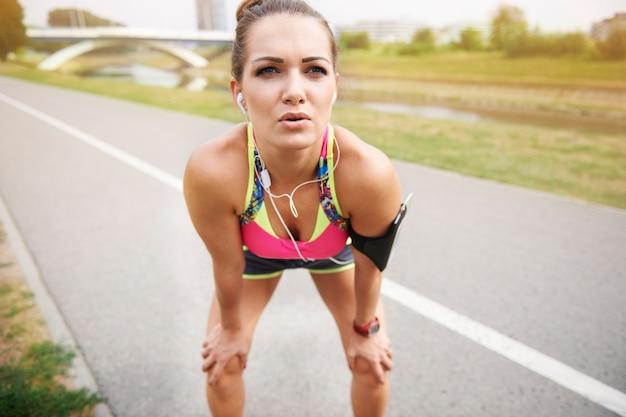 屋外で運動する若い女性。短い休憩と私は私のトレーニングを続けます