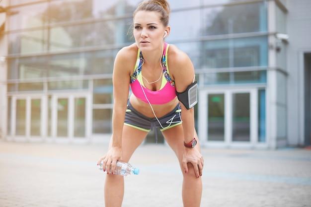 屋外で運動する若い女性。深呼吸するには短い休憩が必要です