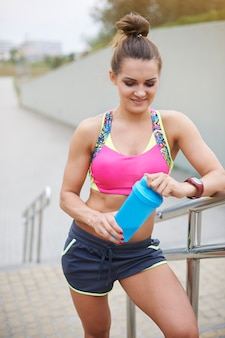 Young woman exercising outdoor. sporty woman holding a bottle full of proteins