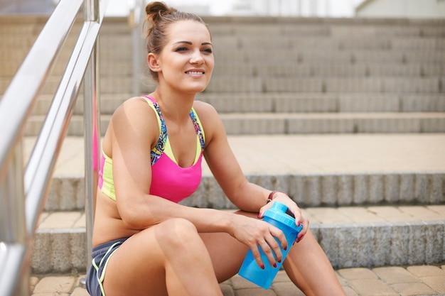 屋外で運動する若い女性。ステップは休憩するのに良い場所です