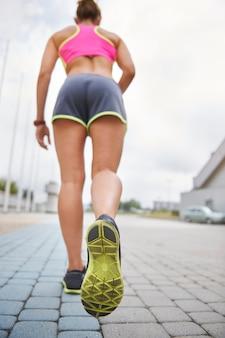 屋外で運動する若い女性。この女性は走っている間非常に持久力があります