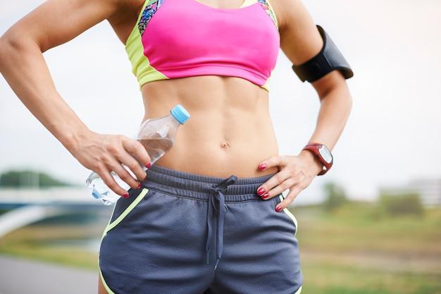 屋外で運動する若い女性。そのような筋肉を持つためにあなたはたくさん運動しなければなりません