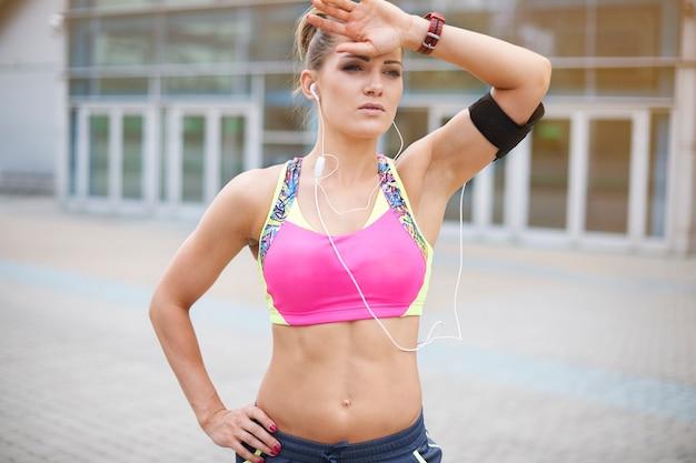 屋外で運動する若い女性。とても疲れていますが、それでも意志に満ちています