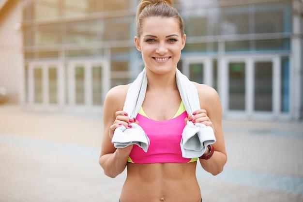 屋外で運動する若い女性。ジムでトレーニングを疲れた後の女性