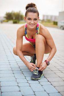 屋外で運動する若い女性。朝のジョギングの準備をしている女性