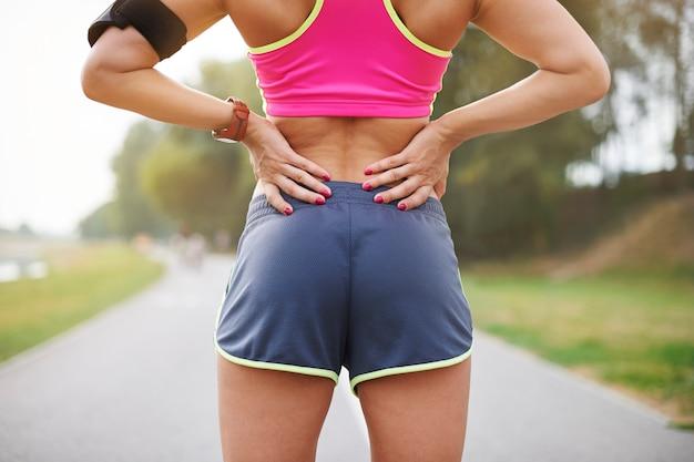 屋外で運動する若い女性。公園の線路を横切って走っている女性