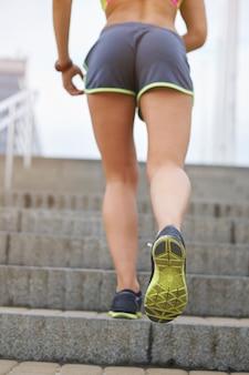屋外で運動する若い女性。街の階段を駆け上がる女性