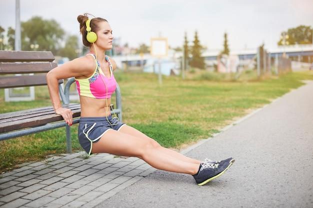 야외 운동하는 젊은 여자. 공원에서 벤치에서 기지개하는 여자