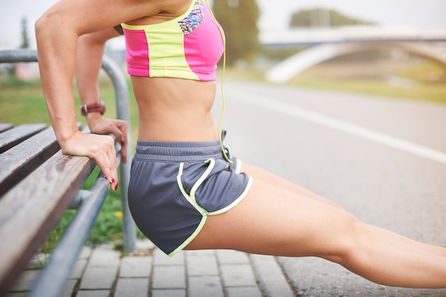 屋外で運動する若い女性。トレーニングはトレーニングの最も重要な部分です