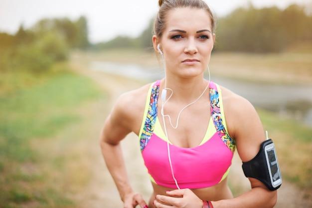 外で運動する若い女性。公園でジョギングする魅力的な女性