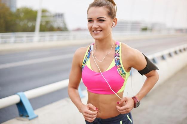 Giovane donna che si esercita all'esterno. il buon umore è il risultato del jogging