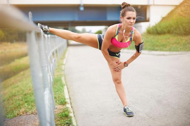 Giovane donna che si esercita all'esterno. un buon allungamento è la base dell'allenamento