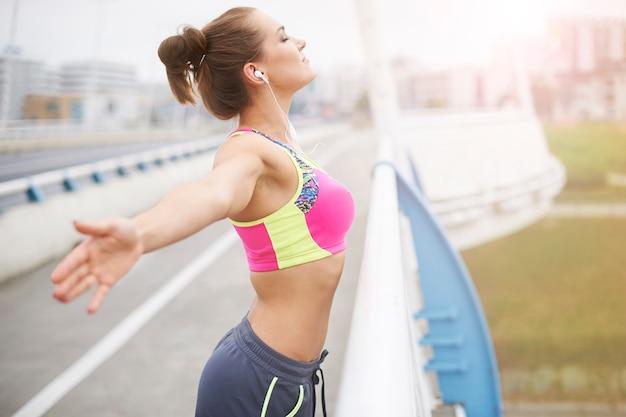 外で運動する若い女性。ジョギングは私にたくさんのエネルギーを与えます