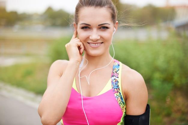 Giovane donna che si esercita all'esterno. la musica è obbligatoria durante il jogging