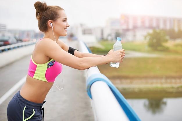 Giovane donna che si esercita all'esterno. sorso d'acqua sul ponte