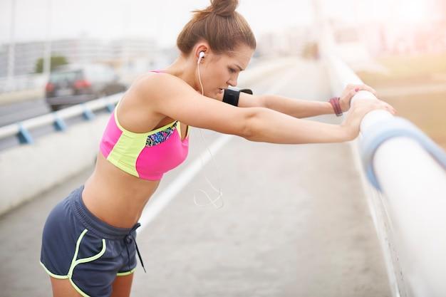 外で運動する若い女性。トレーニングの非常に重要な部分としてのストレッチ