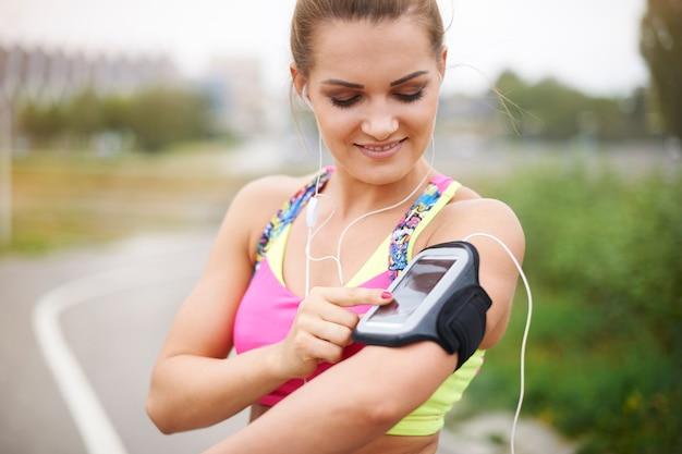 外で運動する若い女性。ジョギングの前にプレイリストをオンにする