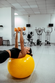 Young woman exercising on a pilates ball holding weights at the gym.