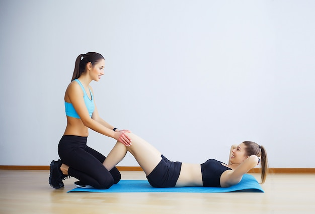 Young woman exercising sit-ups with assistance of female friend in gym.