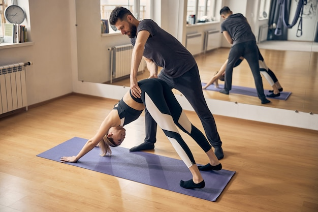 Young woman exercising on special yoga mat while experienced instructor helping her with the pose