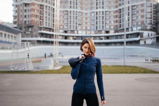 경기장에서 외부 kettlebell와 운동하는 젊은 여자