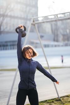 경기장 밖에서 케틀벨을 들고 운동하는 젊은 여성