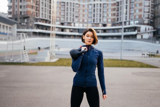 Молодая женщина, тренирующаяся с гирей на улице на стадионе