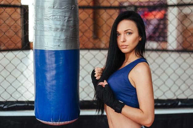 Молодая женщина тренируется с боксерской грушей