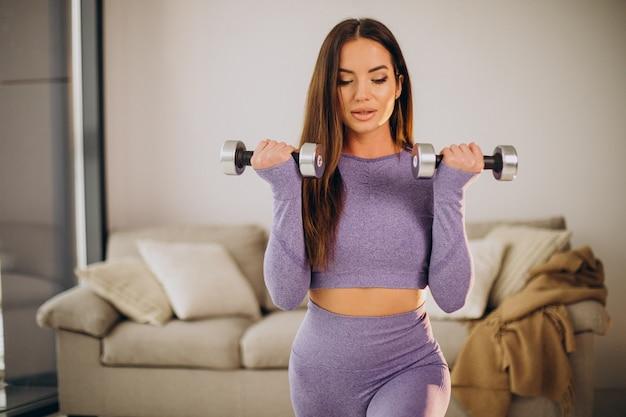 マットの上に自宅でダンベルで運動する若い女性