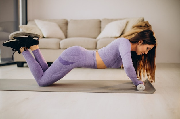 Young woman exercising with dumbbells at home on mat