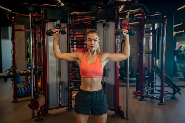 Young woman exercising with dumbbells to strengthen biceps and shoulders in gym