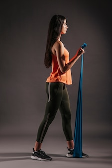 Young woman exercising with elastic band