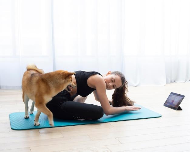 Молодая женщина, тренирующаяся со своей собакой