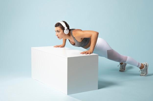 ヘッドフォンをつけて運動する若い女性