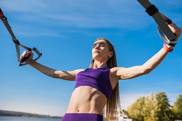 Молодая женщина тренируется с подвеской тренера слинг в парке, недалеко от озера.