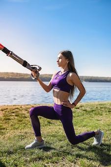 湖の近くの公園でサスペンショントレーナースリングで運動している若い女性。