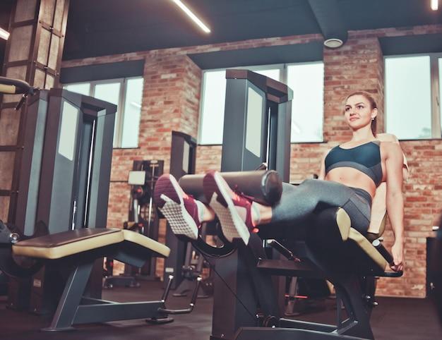 체육관에서 다리 확장 기계 운동 젊은 여자