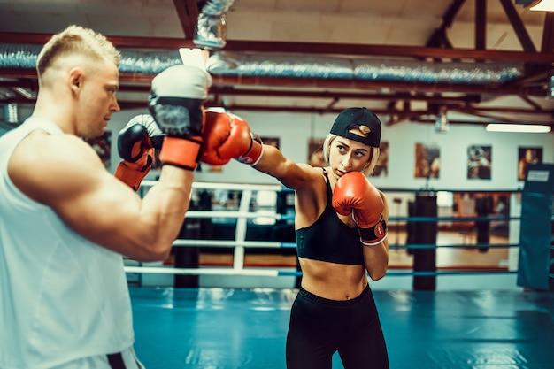 Молодая женщина тренируется с тренером на уроке бокса и самообороны.
