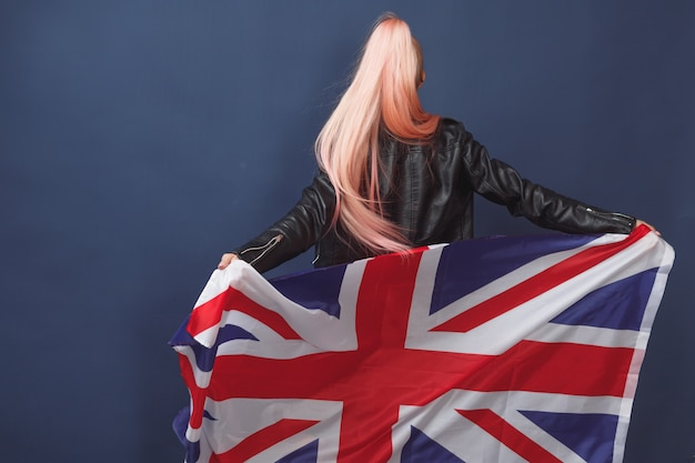 Young woman expat in eyeglasses with great britain flag. studio shot. english language hipster teacher
