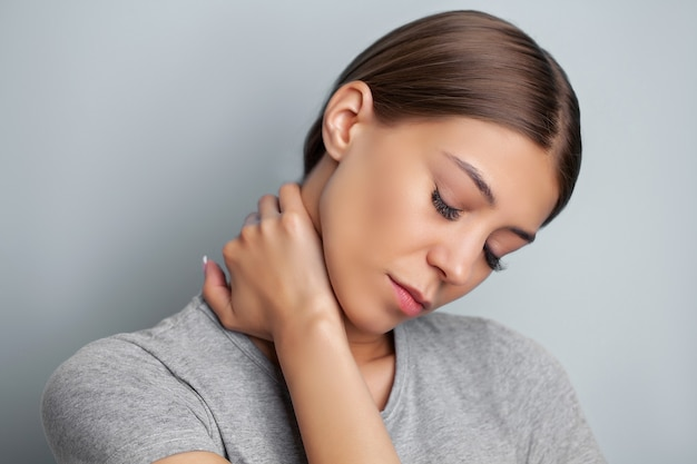 Young woman experiencing severe neck pain while holding her hands.
