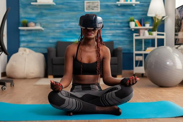 Молодая женщина испытывает виртуальную реальность, тренируя тело и разум, медитируя в позе лотоса, сидя на коврике для йоги в домашней гостиной