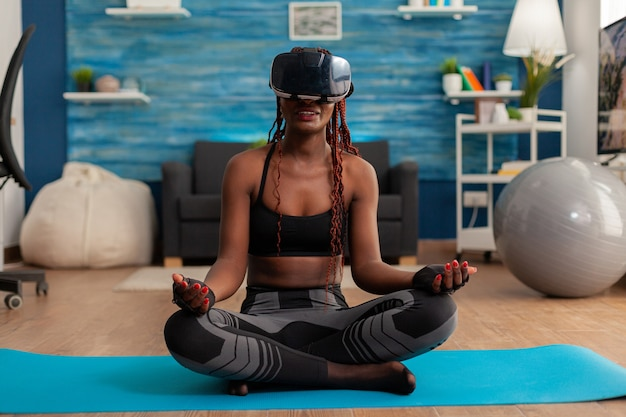 Young woman experiencing virtual reality training body and mind meditating in lotus pose sitting on yoga mat in home living room