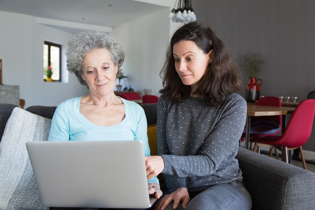 Young woman explaining grandma how to use laptop