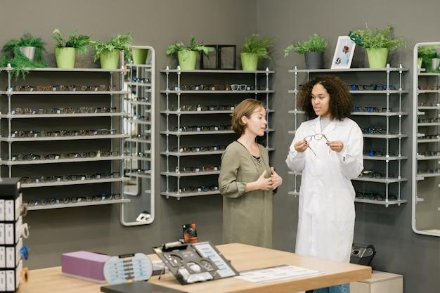 혼혈 컨설턴트가 새로운 안경을 선택하는 동안 찾고있는 것을 설명하는 젊은 여성