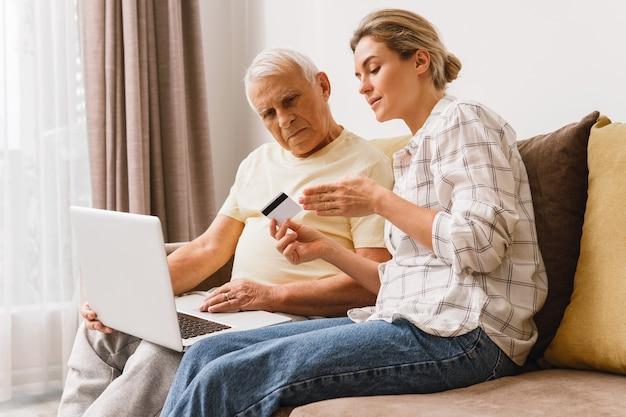 전자 결제 서비스를 사용하는 방법을 노인에게 설명하는 젊은 여성
