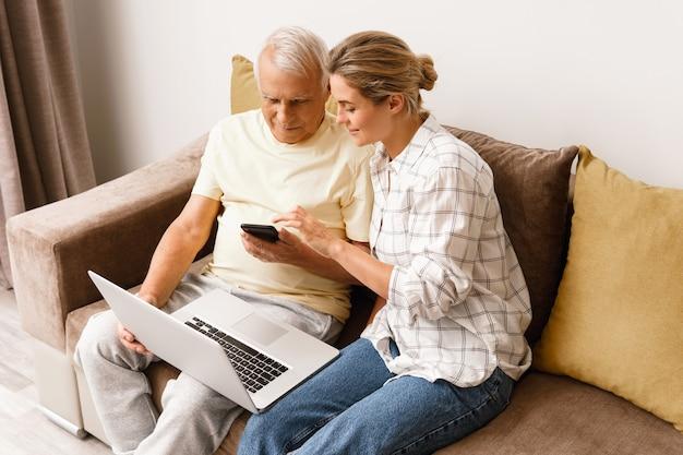 노트북과 스마트폰 사용법을 노인에게 설명하는 젊은 여성